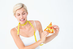 Pretty blonde choosing between eating pizza or not Royalty Free Stock Photo