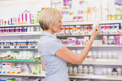 Pretty blonde customer looking at medicine Royalty Free Stock Images