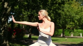 Pretty blonde doing tai chi in the park