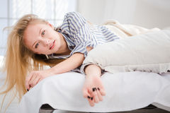 Pretty blonde female waking up lying in bed. Pretty relaxed young blonde female waking up lying in white bed in striped pajamas Royalty Free Stock Photo