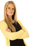 Pretty blonde female wearing yellow glasses with arms folded Royalty Free Stock Photography