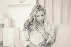 Pretty blonde getting affliction breathing. At home in the living room Royalty Free Stock Photo