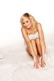 Pretty blonde girl with arms around her knees Royalty Free Stock Photography