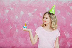 Pretty blonde girl in birthday cap hold cupcake with candle. Pretty blonde girl in birthday cap hold cupcake with single candle on a pink background. Colorful Royalty Free Stock Photo
