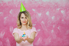 Pretty blonde girl in birthday cap hold cupcake with candle. Pretty blonde girl in birthday cap hold cupcake with single candle on a pink background. Colorful Stock Images