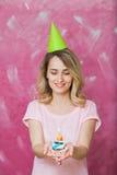 Pretty blonde girl in birthday cap hold cupcake with candle. Pretty blonde girl in birthday cap hold cupcake with single candle on a pink background. Woman Stock Photo