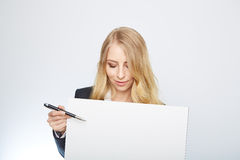 Pretty blonde girl with a blank presentation board Royalty Free Stock Images