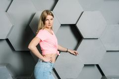 Pretty blonde girl, blue eyes in a pink tank top, in blue jeans posing stock photo