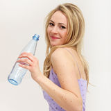 Pretty blonde girl flirts with a smile. Over her bare shoulder while drinking water royalty free stock photos