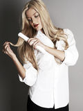 Pretty blonde girl with hair straightener Royalty Free Stock Photos
