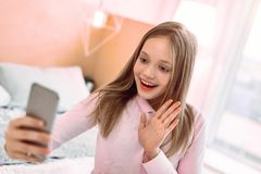 Pretty blonde girl having video communication with her mom royalty free stock image