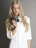Pretty blonde girl holding camera Royalty Free Stock Images