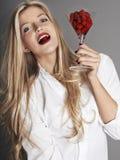 Pretty blonde girl holding glass of raspberries Stock Photo