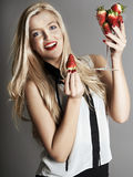 Pretty blonde girl holding glass of Strawberries Royalty Free Stock Photography