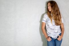 Pretty blonde girl in khaki t-shirt and jeans white wall behind, copy space.  stock photos