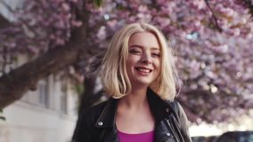 Pretty blonde girl in leather jacket enjoying the cherry blossom in the city, turns to camera and smiles charmingly stock video