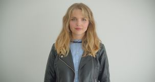 Pretty blonde girl in leather jacket watching into camera being calm isolated on white background. Pretty blonde girl in leather jacket watching into camera stock video