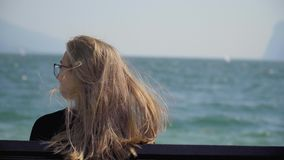 Woman on the bench. Pretty blonde girl with long blonde hair sitting on a bench. Young woman watching people windsurfing in the sea. Handheld shot of lonely stock footage