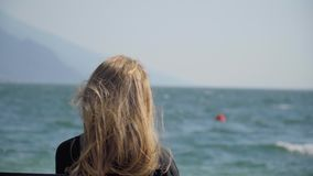 Woman On The Bench. Pretty blonde girl with long blonde hair sitting on a bench. Young woman watching people windsurfing in sea. Handheld shot of lonely female stock footage