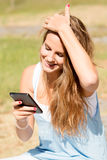 Pretty blonde girl looking the mobile on a sunny day Stock Photo