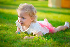 Pretty blonde girl lying on grass Stock Photo