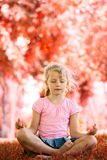 Pretty blonde girl meditating at the park Stock Images