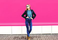 Pretty blonde girl model in full-length posing wearing rock black style jacket, hat on city street over colorful pink wall royalty free stock photography