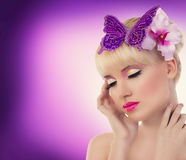 Pretty blonde girl with orchid flower and butterfly Stock Photography