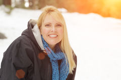 Pretty Blonde Girl Outdoors in Snow Wearing Coat and Scarf Stock Photos