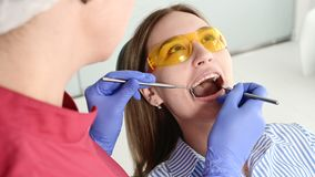 Pretty blonde girl in protective yellow glasses on the stamotologist examined her open mouth. Female dentist examines. The oral cavity of a young patient with stock footage