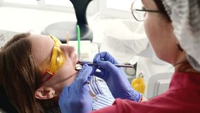 Pretty blonde girl in protective yellow glasses on the stamotologist examined her open mouth. Female dentist examines. The oral cavity of a young patient with stock video