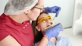 Pretty blonde girl in protective yellow glasses on the stamotologist examined her open mouth. Female dentist examines. The oral cavity of a young patient with stock video footage