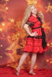 Pretty blonde girl in red fairytale dress standing on orange background with stars stock photos