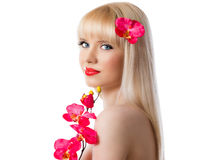 Pretty blonde girl with red orchid flowers on white background Stock Photos