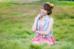 Pretty blonde girl relaxing outdoor sitting in green grass Royalty Free Stock Images