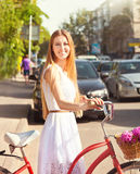 Pretty blonde girl with retro look, bike and basket with flowers Stock Photo