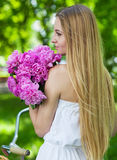 Pretty blonde girl with retro look, bike and basket with flowers Stock Images