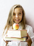 Pretty blonde girl schoolgirl with books and apple. Education. Royalty Free Stock Photography