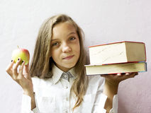 Pretty blonde girl schoolgirl with books and apple. Education. Royalty Free Stock Images