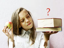 Pretty blonde girl schoolgirl with books and apple. Education. Stock Image