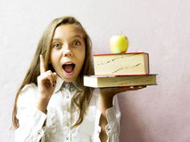 Pretty blonde girl schoolgirl with books and apple. Education. Royalty Free Stock Image