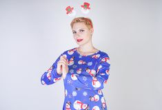 Pretty blonde girl with short hair wearing christmas funny bright dress on white studio background alone stock image