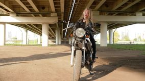 Pretty Blonde Girl Sit Bike City Road Pose Photo. Attractive Caucasian Female Teenager Makeup Motobike Posture. Cute Adolescent Leather Jacket Urban Motorway stock footage