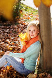 Pretty blonde girl is sitting in autumn park Royalty Free Stock Photography
