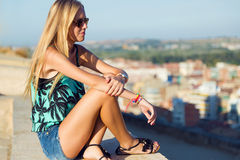 Pretty blonde girl sitting on the roof. Royalty Free Stock Image