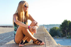 Pretty blonde girl sitting on the roof. Stock Photo