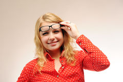 Pretty blonde girl squints in glasses Royalty Free Stock Image