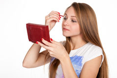 Pretty blonde girl touches up eyelashes Royalty Free Stock Photography