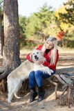 Pretty blonde girl walking with dog in the forest. Animal concept. Beautiful girl with long hair having fun with doggie in the forest. Young woman with puppy Royalty Free Stock Image