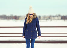 Pretty blonde girl wearing a jacket, hat and sunglasses Royalty Free Stock Photo